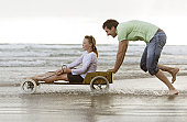 Father pushing daughter in go-kart on beach