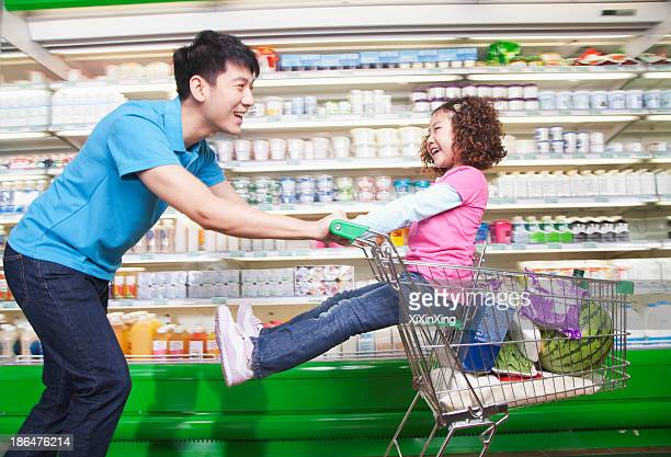 Father Pushing Daughter in Shopping Cart Inside Supermarket, Laughing