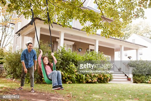 Father Pushing Daughter On Garden Swing At Home : Stock Photo