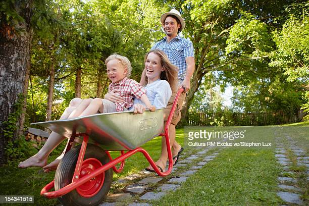 Father pushing family in wheelbarrow