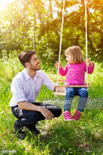 Father pushing her daughter on swing.