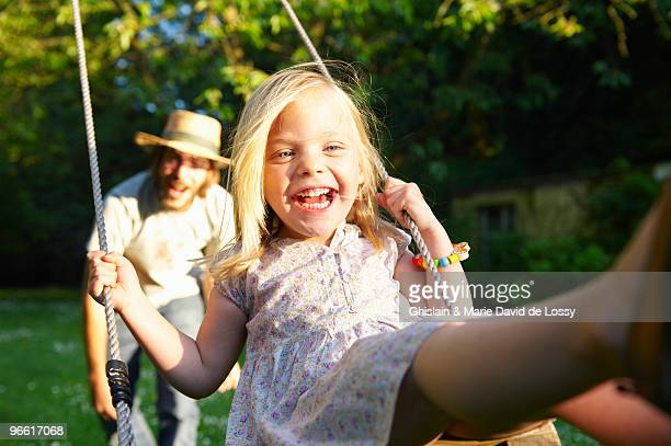 Father pushing his girl on the swing