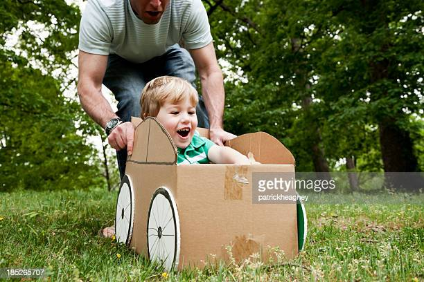 Père poussant son fils dans une boîte en carton sur de l'herbe