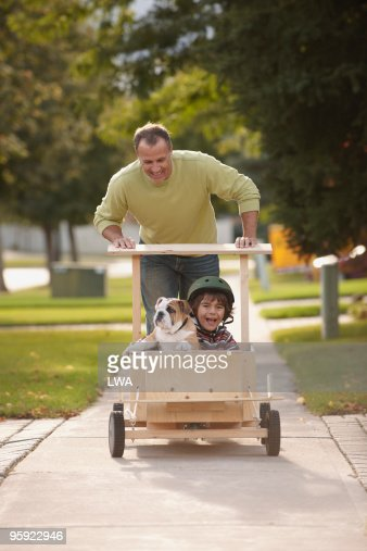 Father Pushing Son and Puppy In Soap Box Car : Stock Photo