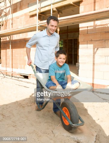 Father Pushing Son In Wheelbarrow By House Under