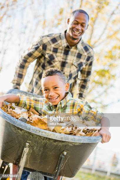 Father pushing son in wheelbarrow in autumn leaves