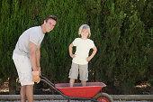 Father pushing son in wheelbarrow