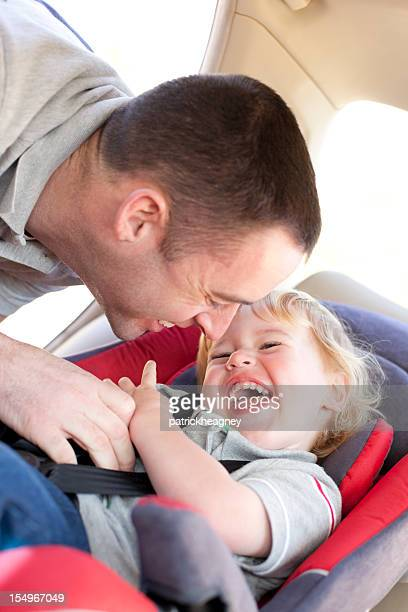 Father puts child in car seat