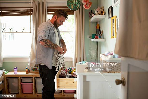 Father putting away child's laundry