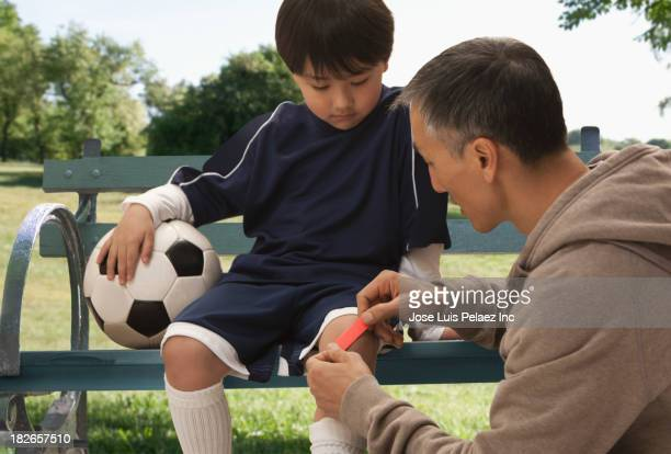 Father putting bandage on son's knee