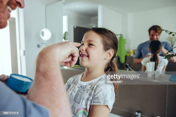 Father putting facial cream on daughter?s face