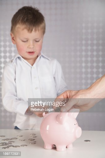 Father putting money in son's piggy bank. : Stock Photo