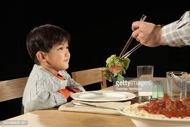 Padre al figlio di insalata di inserimento (3-5) piatto, ragazzo sorridente