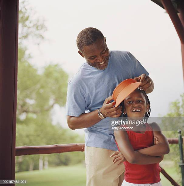 Father putting sun visor on girl (4-6)