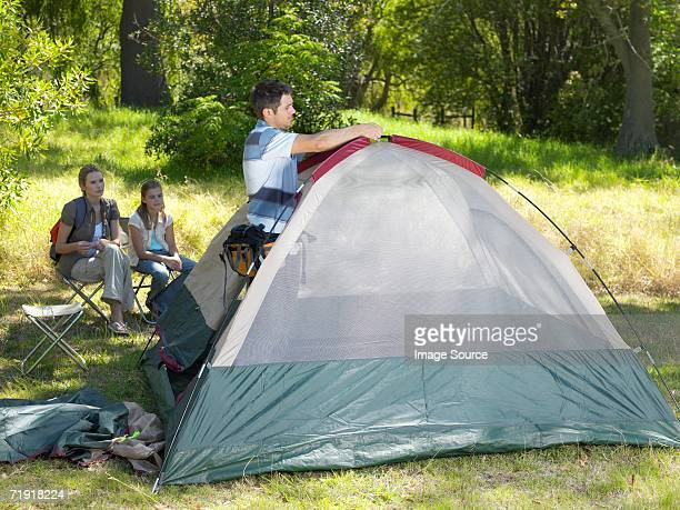 Father putting up tent