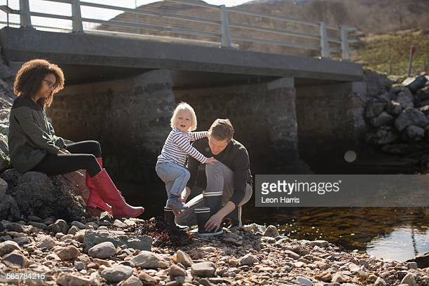 Father putting wellingtons on son by footbridge