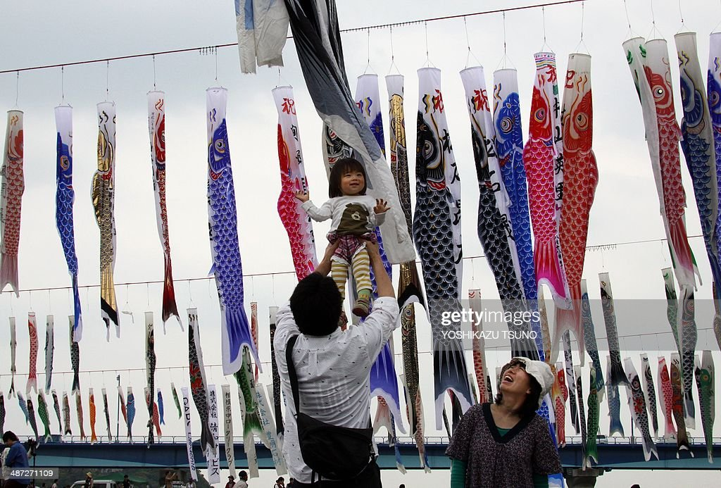 A father raises his daughter in the air under colorful carp streamers flying above a riverside park in Sagamihara, suburban Tokyo on April 29, 2014 ahead of May 5 Children's Day in Japan. Some 1,200 carp streamers fluttered along the river as part of an annual event for Japan's week-long holidays, Golden Week. 'Koinobori' (carp streamers) reflect the parents' wishes for boys to grow up as strong as the carp. AFP PHOTO / Yoshikazu TSUNO