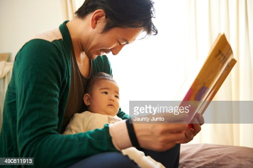 Father reading a picture book for his baby