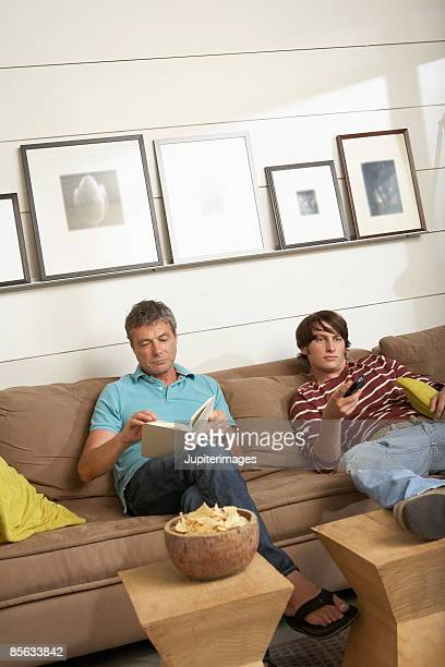 Father reading and son holding remote control