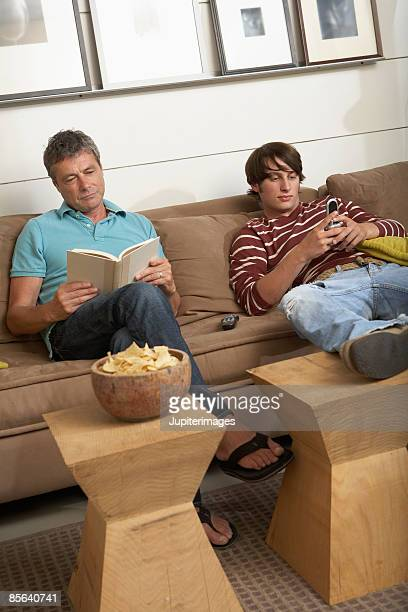 Father reading and son text messaging