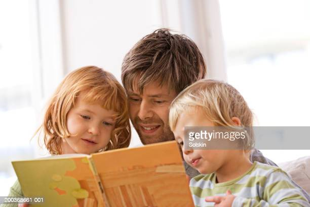 Father reading book to son and daughter (2-5), close-up