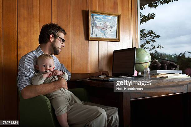 Father reading newspaper, with baby girl (6-9 months) on lap