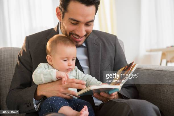 Father reading to baby on sofa