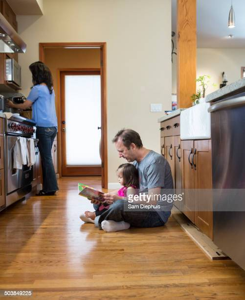 Father reading to daughter in kitchen