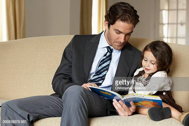 Father reading to daughter (2-4) on sofa