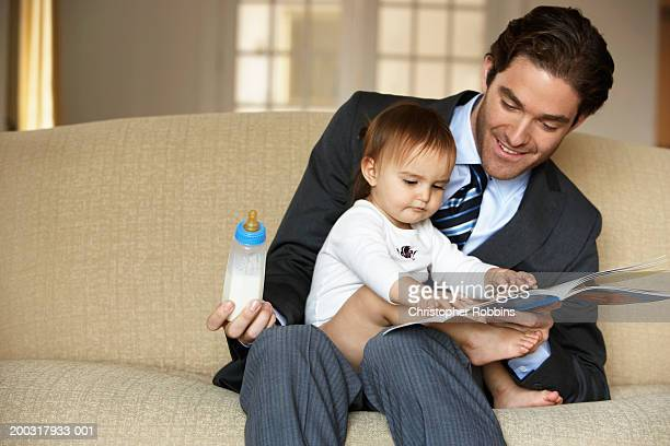 Father reading to daughter (15-18 months) on sofa, smiling