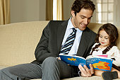 Father reading to daughter (2-4) on sofa, smiling