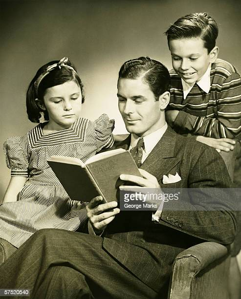 Père lisant à son fils (4-5) et fille (6-7