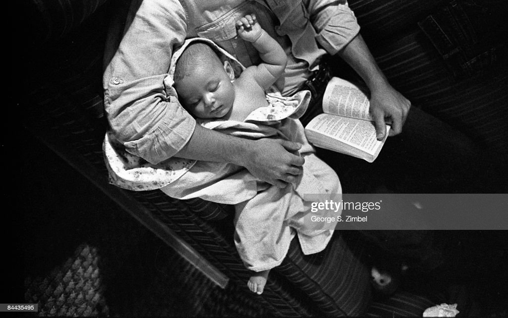 A father reads a book while holding his sleepoing son on his lap, 1981. Montreal.
