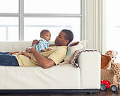 Father relaxing with son (6-12 months) on sofa