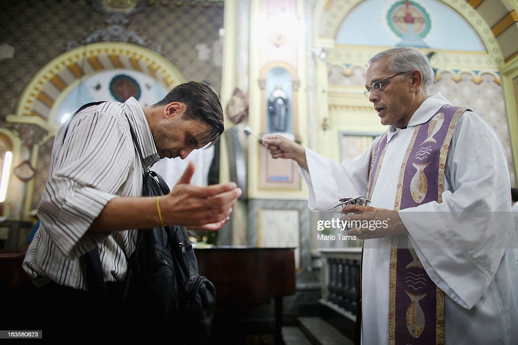 Father Reni Nogueira dos Santos tosses holy water on a worshiper in the Church of Our Lady of the Rosary of Black Men during Mass on March 12, 2013 in Sao Paulo, Brazil. The current structure was built by African-Brazilian Catholics in 1906 while the original church, which was demolished, was constructed by slaves of African descent. Brazil has more Catholics than any other country in the world and supporters hope Sao Paulo Archbishop Cardinal Odilo Pedro Scherer will be chosen as the next Pope during the papal conclave.