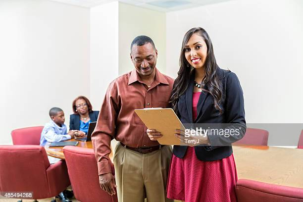 Father Reviews School Reports with Administrator