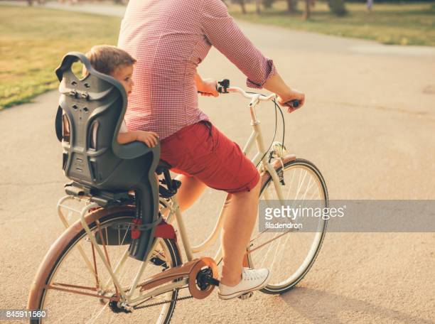 Father riding a bicycle with his son on a baby seat