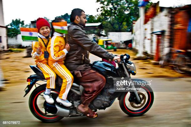 A father riding a motorcycle transports his two sons carrying Indian national flags with pride on January 26 2012 at Varanasi Uttar Pradesh India