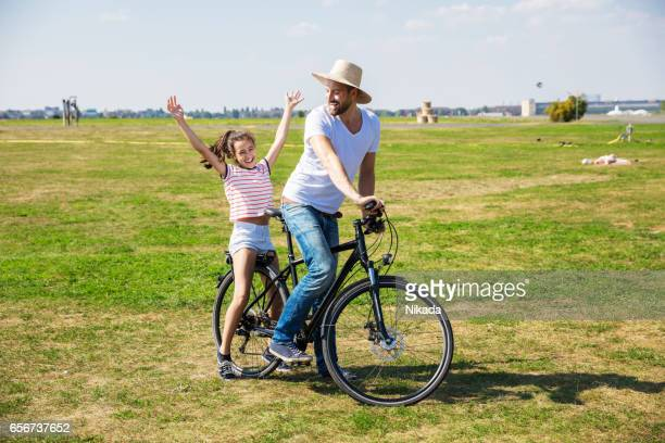 father riding bicycle with happy daughter