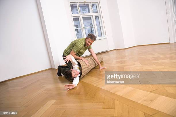 father rolling his son into carpet