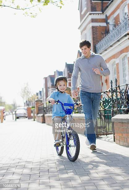 Father running alongside son riding bicycle on sidewalk