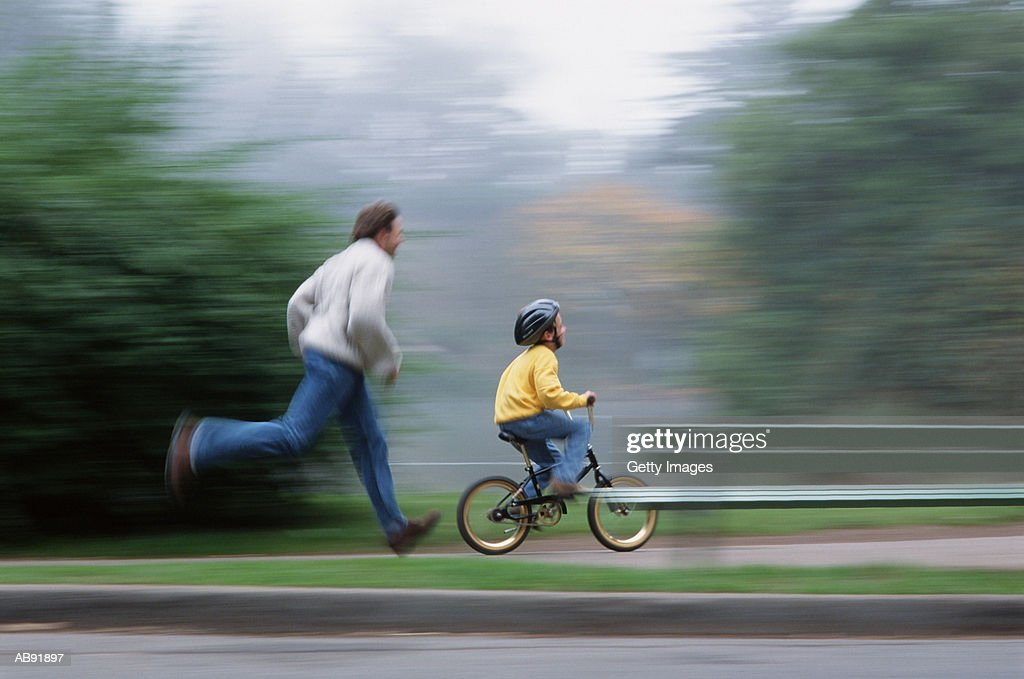 Father running by son (7-9) riding bicycle