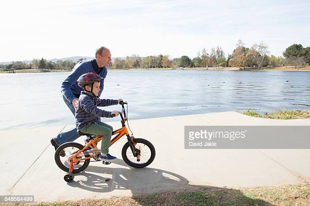 Father running next to son on bicycle in park