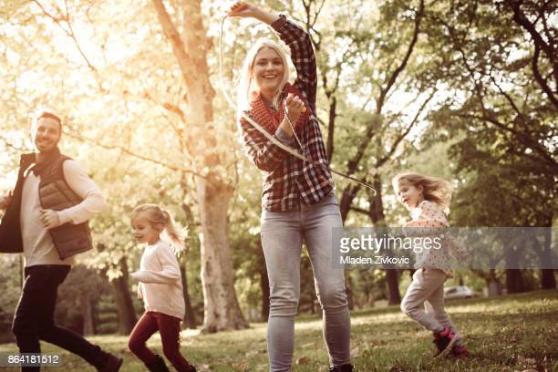 Father running with daughters trough park and mother holding jump rope.