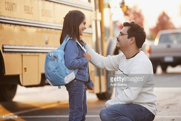 Father saying goodbye to daughter in front of school bus