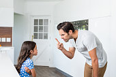 Father scolding daughter at home