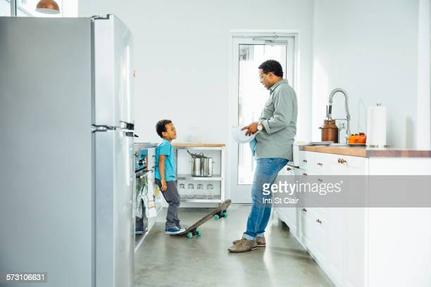 Father scolding son for skateboarding in kitchen