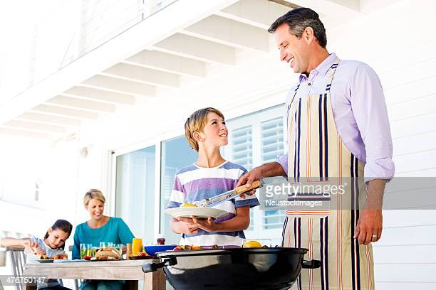 Father Serving Barbecued Burger To Son On Porch
