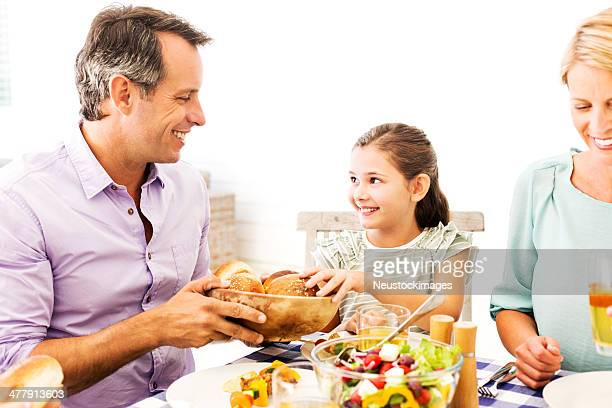 Father Serving Bread To Daughter During Lunch On Patio