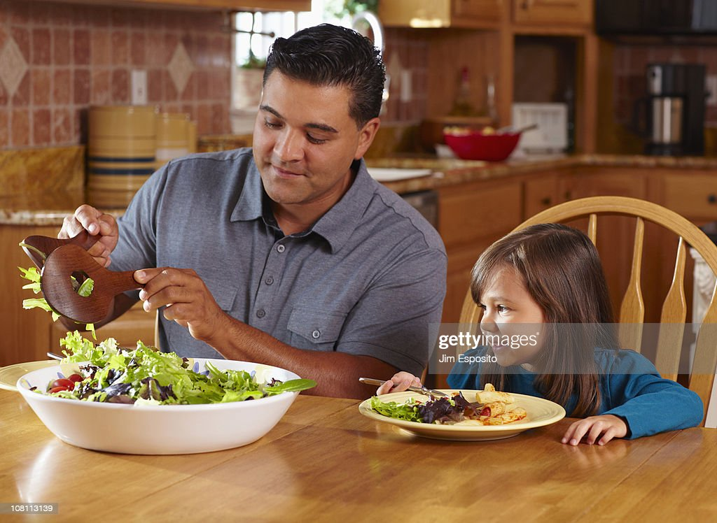 Father serving daughter salad at dinner table : Stock Photo
